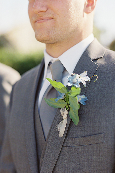 San diego outdoor rustic wedding groom grey notch lapel suit with a white dress shirt and matching vest with a long grey tie and blue floral boutonniere close up