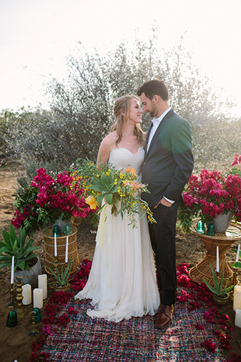Anza valley rustic outdoor wedding at the alpaca farm bride strapless chiffon gown with a sweetheart necklace holding green and yellow floral bridal bouquet with groom navy blue suit with white dress shirt and no tie standing by pink floral arch for ceremony