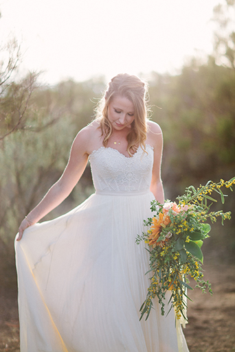 Anza valley rustic outdoor wedding at the alpaca farm bride strapless chiffon gown with a sweetheart neckline holding green and yellow floral bridal bouquet while holding up side of dress wedding photo idea for bride