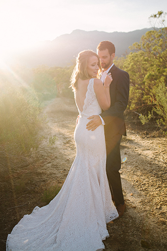 Anza valley rustic outdoor wedding at the alpaca farm bride chiffon gown with lace straps and open back design with wedding ring and groom navy blue suit with white dress shirt and no tie wedding photo idea hugging at sunset