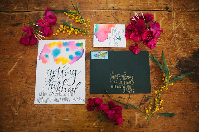 Anza valley rustic outdoor wedding at the alpaca farm white wedding invtiations with blue pink and yellow colors on top and black calligraphy writing with black envelope and pink flowers on brown wood table wedding photo idea
