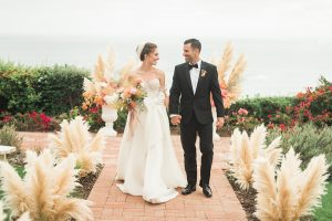 Dana point wedding at doheny house bride strapless a line gown with a beaded bodice and long veil with lace arm sleeves with groom black tuxedo with white dress shirt and black bow tie with orange floral boutonniere bride holding white and peach floral bridal bouquet walking down aisle holding hands