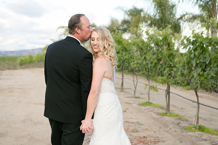 Temecula outdoor wedding at villa de amore vineyard bride strapless mermaid style gown with crystal belt and medium veil with groom black tuxedo with white dress shirt and white bow tie with matching vest and white floral boutonniere kissing bride