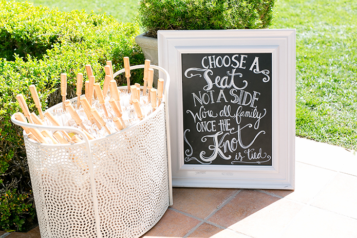 Temecula outdoor wedding at villa de amore vineyard black and white chalkboard sign with writing for guests seating and white umbrellas in white basket wedding photo idea