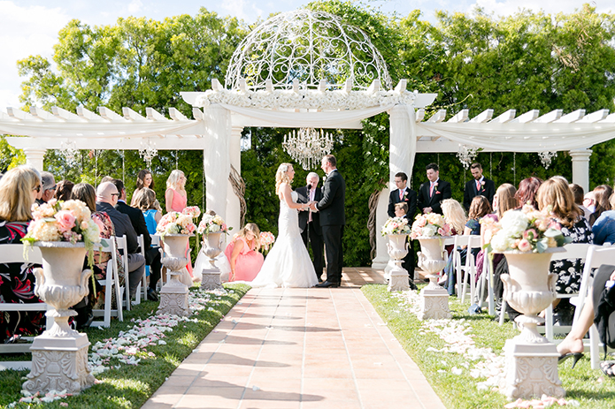 Temecula outdoor wedding at villa de amore vineyard bride strapless mermaid style gown with crystal belt and medium veil with groom black tuxedo with white dress shirt and white bow tie with matching vest and white floral boutonniere holding hands under white gazebo during ceremony