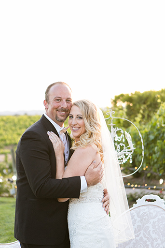 Temecula outdoor wedding at villa de amore vineyard bride strapless mermaid style gown with crystal belt and medium veil with groom black tuxedo with white dress shirt and white bow tie with matching vest and white floral boutonniere standing by white lounge furniture decor