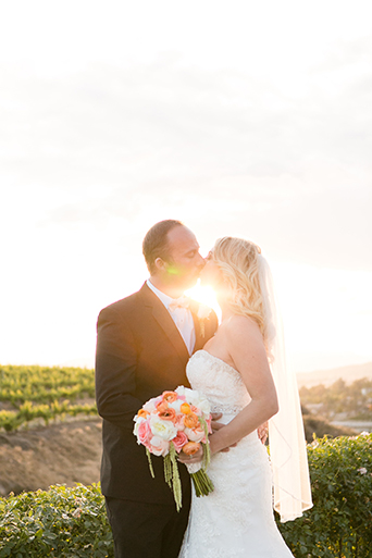 Temecula outdoor wedding at villa de amore vineyard bride strapless mermaid style gown with crystal belt and medium veil with groom black tuxedo with white dress shirt and white bow tie with matching vest and white floral boutonniere kissing at sunset