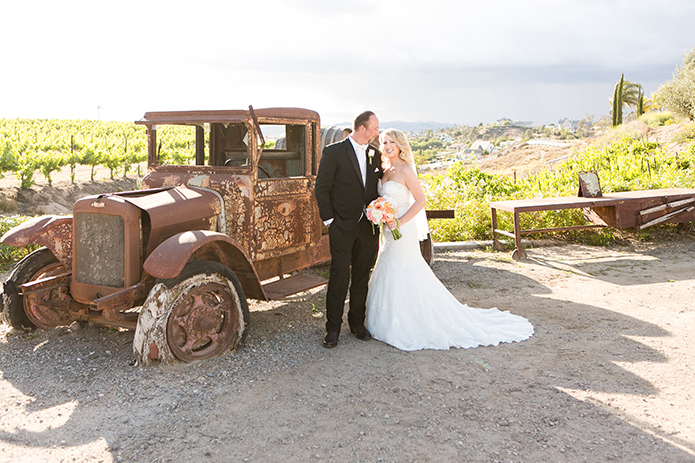 Temecula outdoor wedding at villa de amore vineyard bride strapless mermaid style gown with crystal belt and medium veil with groom black tuxedo with white dress shirt and white bow tie with matching vest and white floral boutonniere standing by brown vintage truck with wine barrels