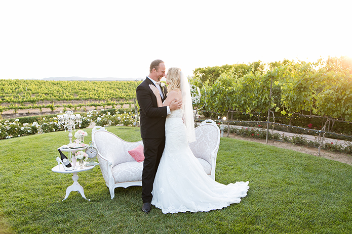 Temecula outdoor wedding at villa de amore vineyard bride strapless mermaid style gown with crystal belt and medium veil with groom black tuxedo with white dress shirt and white bow tie with matching vest and white floral boutonniere kissing by white lounge furniture decor