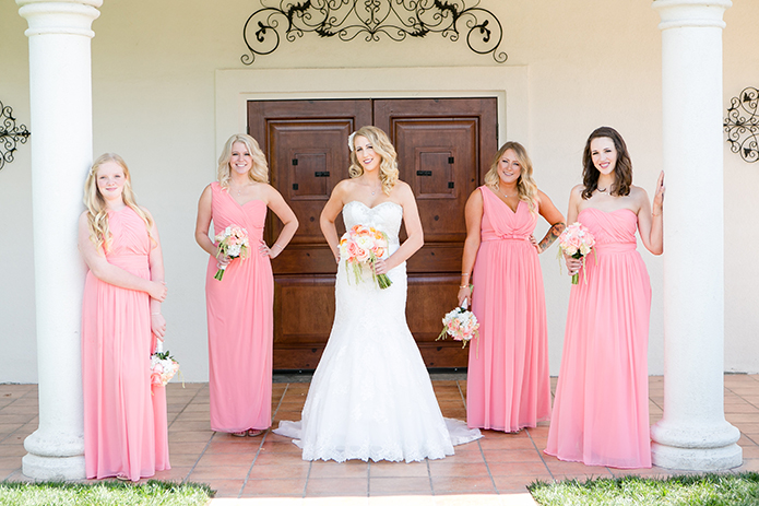 Temecula outdoor wedding at villa de amore vineyard bride strapless mermaid style gown with crystal belt and medium veil with bridesmaids long pink dresses holding white and pink floral bridal bouquets