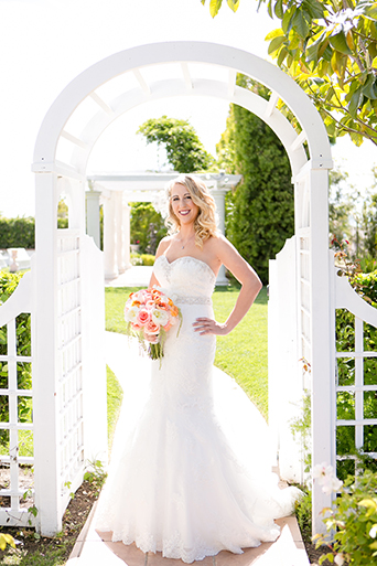 Temecula outdoor wedding at villa de amore vineyard bride strapless mermaid style gown with crystal belt and medium veil holding bottom of dress with white and pink floral bridal bouquet