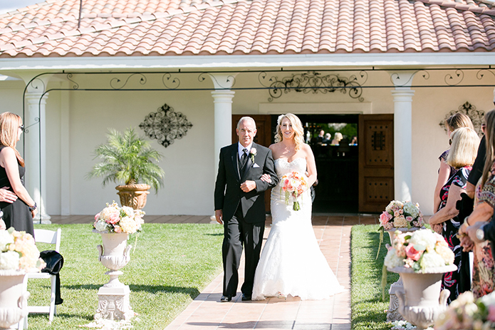 Temecula outdoor wedding at villa de amore vineyard bride strapless mermaid style gown with crystal belt and medium veil holding bottom of dress with white and pink floral bridal bouquet walking down with aisle with dad black suit