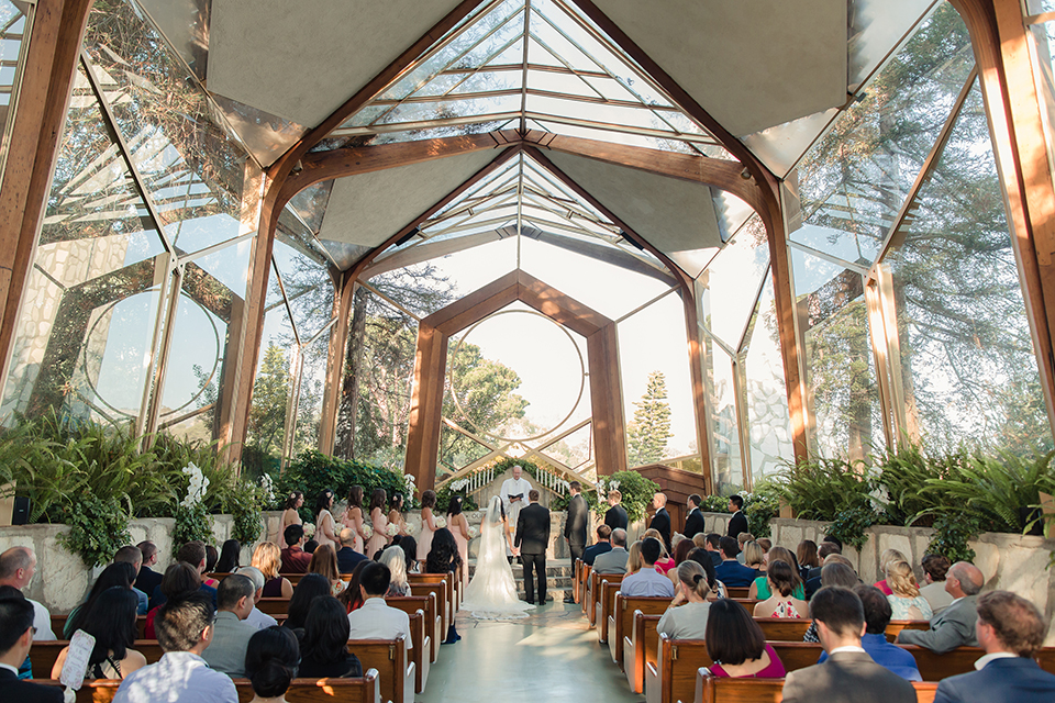Summer outdoor wedding at south coast botanic gardens bride mermaid style gown with lace detail and sweetheart neckline with crystal belt and groom black suit with matching vest with white dress shirt and black bow tie with white floral boutonniere standing during ceremony