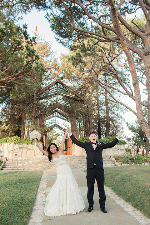 Summer outdoor wedding at south coast botanic gardens bride mermaid style gown with lace detail and sweetheart neckline with crystal belt and groom black suit with matching vest with white dress shirt and black bow tie with white floral boutonniere cheering after ceremony bride with white floral bridal bouquet