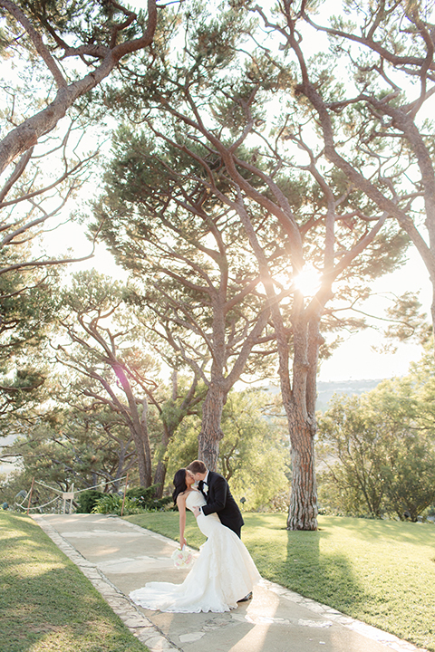 Summer outdoor wedding at south coast botanic gardens bride mermaid style gown with lace detail and sweetheart neckline with crystal belt and groom black suit with matching vest with white dress shirt and black bow tie with white floral boutonniere kissing
