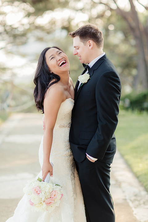 Summer outdoor wedding at south coast botanic gardens bride mermaid style gown with lace detail and sweetheart neckline with crystal belt and groom black suit with matching vest with white dress shirt and black bow tie with white floral boutonniere laughing