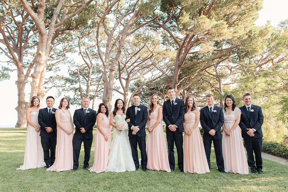 Summer outdoor wedding at south coast botanic gardens bride mermaid style gown with lace detail and sweetheart neckline with crystal belt and groom black suit with matching vest with white dress shirt and black bow tie with white floral boutonniere with bridesmaids blush pink long dresses and groomsmen black suits with black bow ties