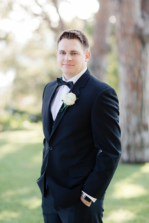 Summer outdoor wedding at south coast botanic gardens groom black suit with notch lapel and matching vest with white dress shirt and black bow tie with white floral boutonniere