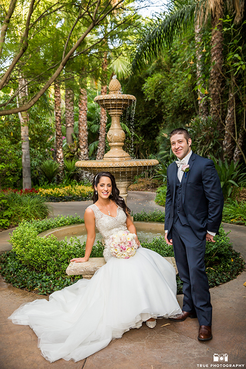 San diego outdoor wedding at the grand tradition bride mermaid style gown with illusion back and straps with plunging neckline and groom navy suit with matching vest and white dress shirt with white bow tie and white floral boutonniere sitting by fountain