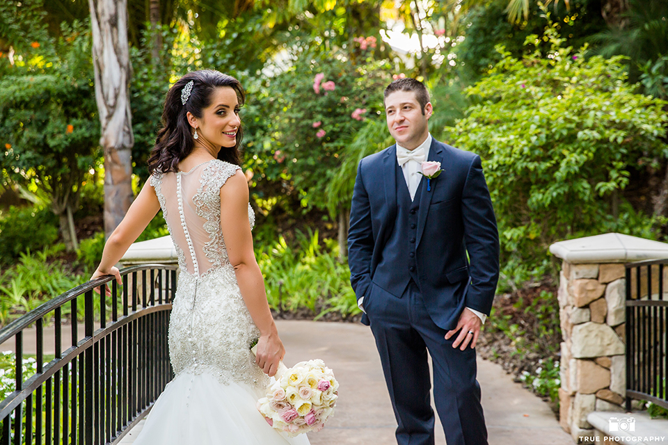 San diego outdoor wedding at the grand tradition bride mermaid style gown with illusion back and straps with plunging neckline and groom navy suit with matching vest and white dress shirt with white bow tie and white floral boutonniere bride holding white floral bridal bouquet