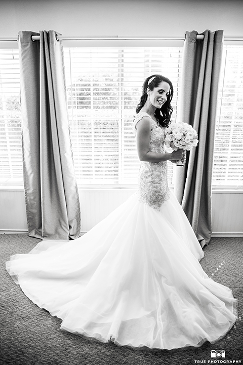 San diego outdoor wedding at the grand tradition bride mermaid style gown with illusion back and straps with plunging neckline holding white floral bridal bouquet black and white photo