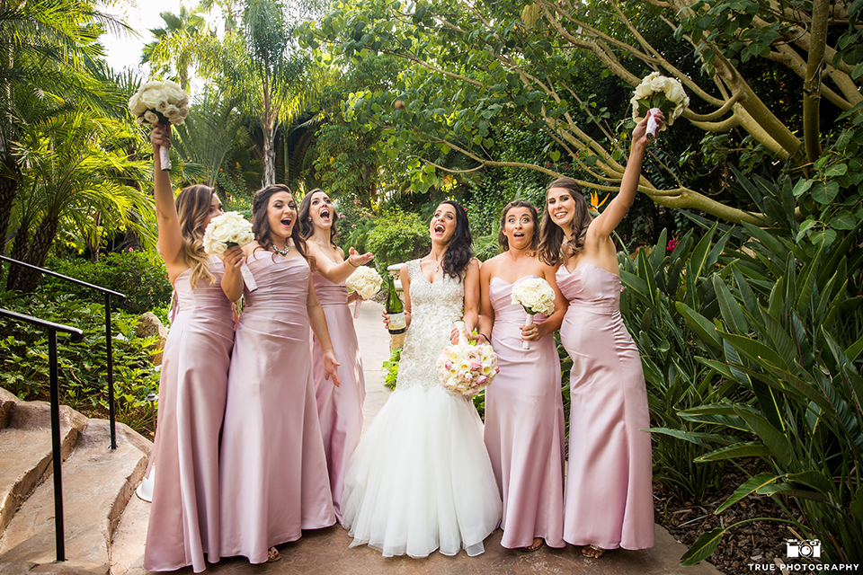 San diego outdoor wedding at the grand tradition bride mermaid style gown with illusion back and straps with plunging neckline holding white floral bridal bouquet with bridesmaids long pink dresses with floral bouquets
