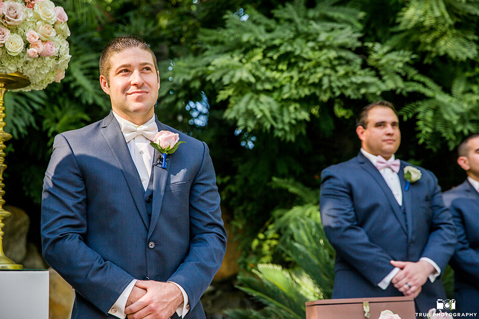 San diego outdoor wedding at the grand tradition groom navy suit with matching vest and white dress shirt with white bow tie and white floral boutonniere standing watching bride walk down the aisle