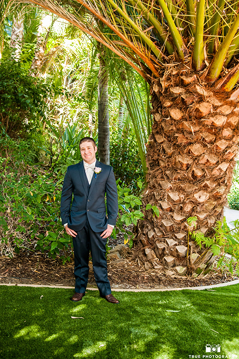 San diego outdoor wedding at the grand tradition groom navy suit with matching vest and white dress shirt with white bow tie and white floral boutonniere