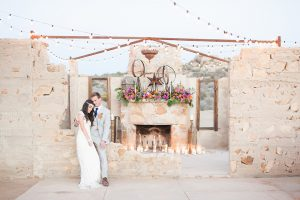Moroccan inspired outdoor wedding shoot at the ruin venue bride lace form fitting gown with plunging neckline and beaded short sleeves with crystal headpiece and groom light grey suit with matching vest and white dress shirt with long blue tie and bright orange floral boutonniere sitting by ceremony set up with white candle decor and hanging lights