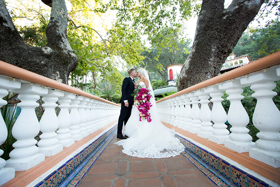 Rancho las lomas outdoor wedding shoot bride strapless tulle ballgown with beaded bodice and sweetheart neckline with long lace detail veil and groom black notch lapel tuxedo with white dress shirt and black bow tie with bright pink floral boutonniere hugging on bridge bride holding bright pink floral bridal bouquet