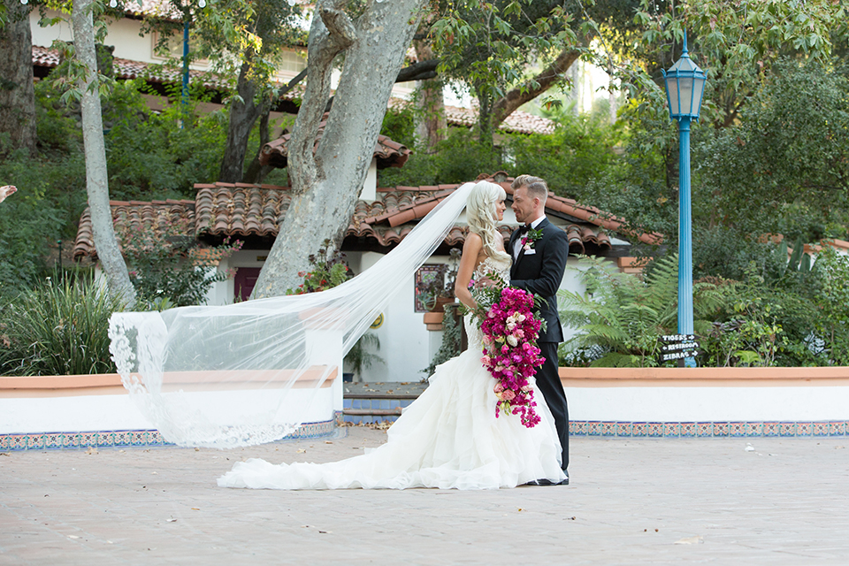 Rancho las lomas outdoor wedding shoot bride strapless tulle ballgown with beaded bodice and sweetheart neckline with long lace detail veil and groom black notch lapel tuxedo with white dress shirt and black bow tie with bright pink floral boutonniere bride holding bright pink floral bridal bouquet