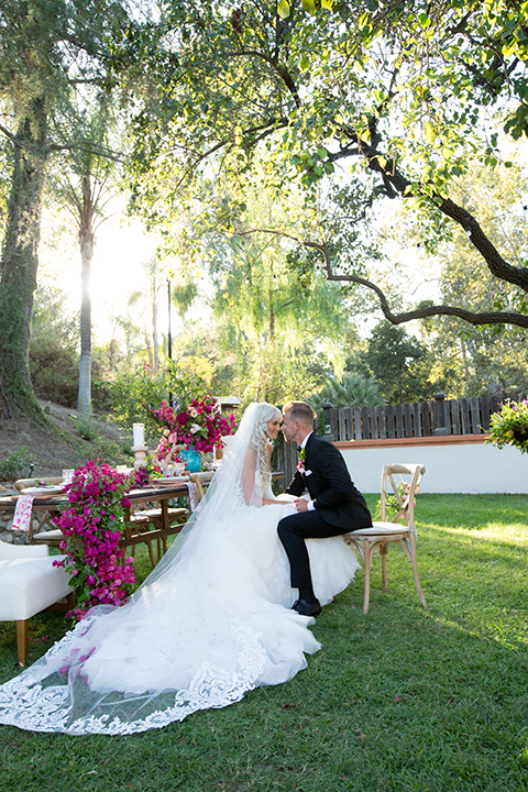 Rancho las lomas outdoor wedding shoot bride strapless tulle ballgown with beaded bodice and sweetheart neckline with long lace detail veil and groom black notch lapel tuxedo with white dress shirt and black bow tie with bright pink floral boutonniere bride holding bright pink floral bridal bouquet sitting at table