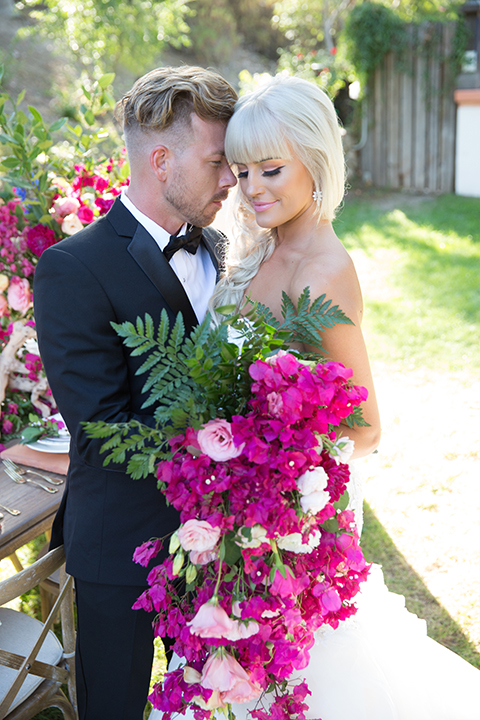 Rancho las lomas outdoor wedding shoot bride strapless tulle ballgown with beaded bodice and sweetheart neckline with long lace detail veil and groom black notch lapel tuxedo with white dress shirt and black bow tie with bright pink floral boutonniere bride holding bright pink floral bridal bouquet standing by table