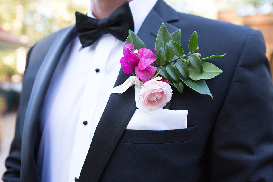 Rancho las lomas outdoor wedding shoot groom black notch lapel tuxedo with white dress shirt and black bow tie with bright pink and light pink floral boutonniere close up