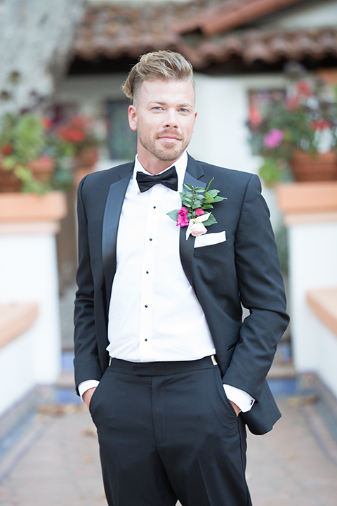 Rancho las lomas outdoor wedding shoot groom black notch lapel tuxedo with white dress shirt and black bow tie with bright pink and light pink floral boutonniere