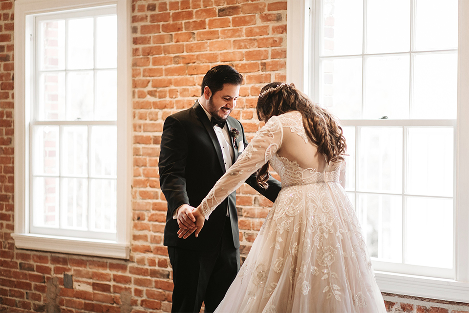 Orange county wedding at the estate on second bride lace ball gown with long sleeves and high neckline with crystal hair piece and groom black tuxedo with white dress shirt and black bow tie with white pocket square holding hands and admiring during first look