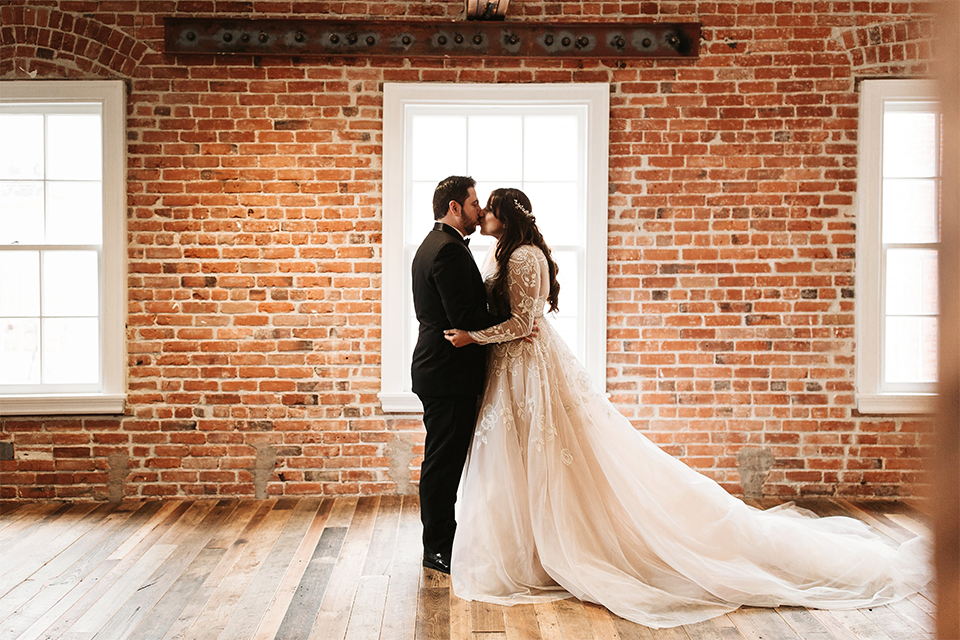 Orange county wedding at the estate on second bride lace ball gown with long sleeves and high neckline with crystal hair piece and groom black tuxedo with white dress shirt and black bow tie with white pocket square kissing after first look