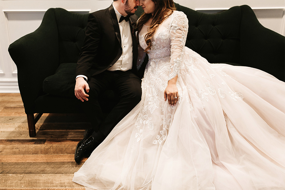 Orange county wedding at the estate on second bride lace ball gown with long sleeves and high neckline with crystal hair piece and groom black tuxedo with white dress shirt and black bow tie with white pocket square sitting on couch