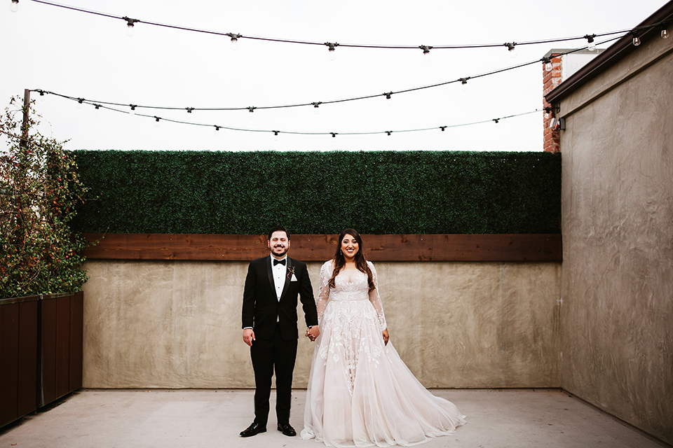 Orange county wedding at the estate on second bride lace ball gown with long sleeves and high neckline with crystal hair piece and groom black tuxedo with white dress shirt and black bow tie with white pocket square standing holding hands