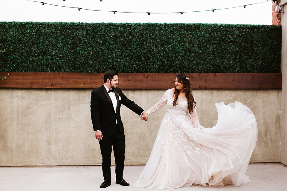 Orange county wedding at the estate on second bride lace ball gown with long sleeves and high neckline with crystal hair piece and groom black tuxedo with white dress shirt and black bow tie with white pocket square standing and holding hands
