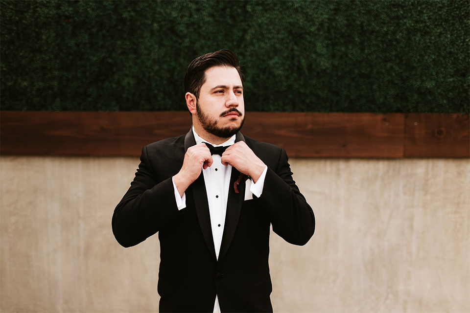 Orange county wedding at the estate on second groom black notch lapel tuxedo with white dress shirt and black bow tie with white pocket square fixing bow tie