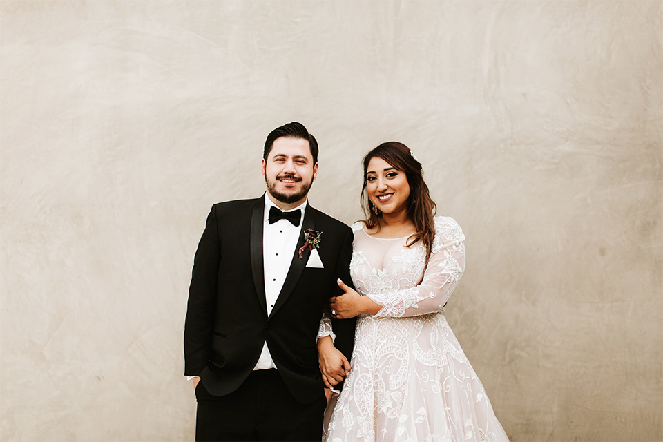 Orange county wedding at the estate on second bride lace ball gown with long sleeves and high neckline with crystal hair piece and groom black tuxedo with white dress shirt and black bow tie with white pocket square hugging and smiling