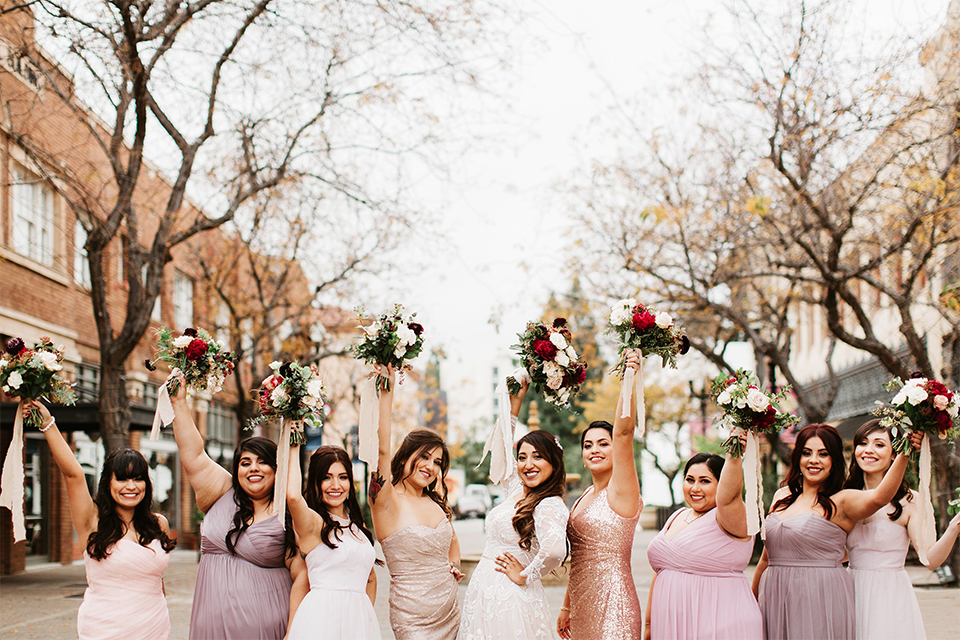 Orange county wedding at the estate on second bride lace ball gown with long sleeves and high neckline with crystal hair piece holding pink and red floral bridal bouquet with bridesmaids long mix and matched dresses pink and gold and purple holding floral bouquets cheering