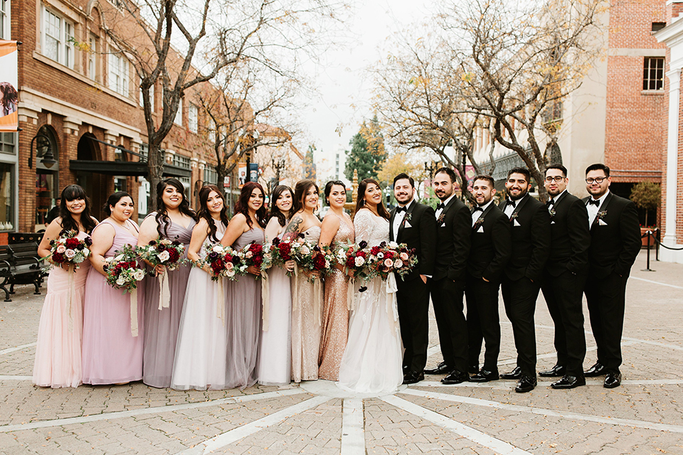 Orange county wedding at the estate on second bride lace ball gown with long sleeves and high neckline with crystal hair piece and groom black tuxedo with white dress shirt and black bow tie with white pocket square with bridesmaids mix and matched pink and gold dresses and groomsmen black tuxedos with white shirts and black bow ties