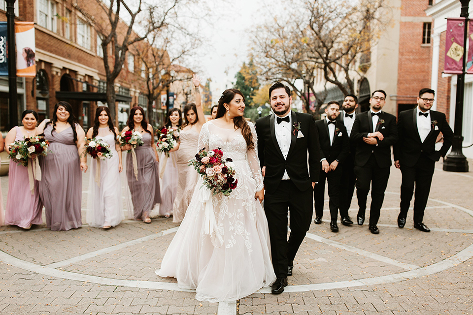 Orange county wedding at the estate on second bride lace ball gown with long sleeves and high neckline with crystal hair piece and groom black tuxedo with white dress shirt and black bow tie with white pocket square with bridesmaids mix and matched dresses with groomsmen black tuxedos with white shirts and black bow ties walking bride holding pink and red floral bridal bouquet