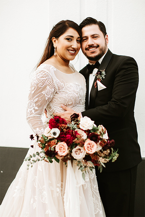 Orange county wedding at the estate on second bride lace ball gown with long sleeves and high neckline with crystal hair piece and groom black tuxedo with white dress shirt and black bow tie with white pocket square hugging bride holding pink and red floral bridal bouquet