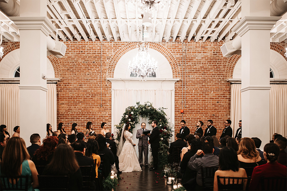 Orange county wedding at the estate on second bride lace ball gown with long sleeves and high neckline with crystal hair piece and groom black tuxedo with white dress shirt and black bow tie with white pocket square holding hands during ceremony