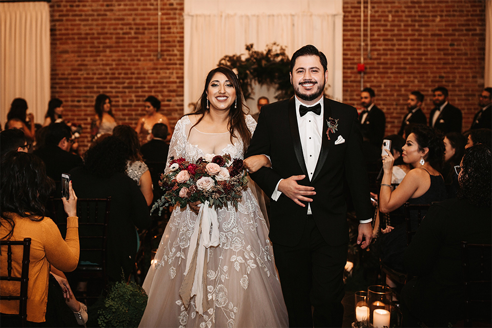 Orange county wedding at the estate on second bride lace ball gown with long sleeves and high neckline with crystal hair piece and groom black tuxedo with white dress shirt and black bow tie with white pocket square walking back down the aisle after ceremony