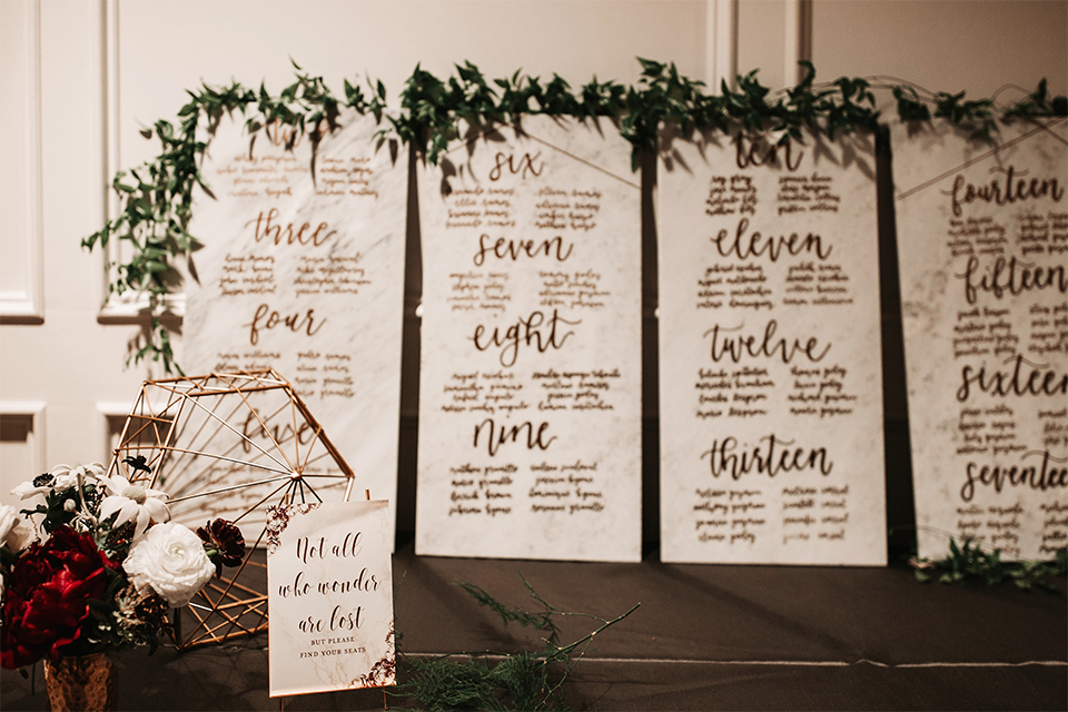 Orange county wedding at the estate on second reception decor table seating chart with white signs and black calligraphy writing and greenery floral decor wedding photo idea