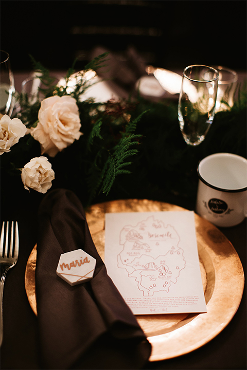 Orange county wedding at the estate on second dark brown wood table with gold place settings and white and green flower centerpiece decor with white glasses and candles